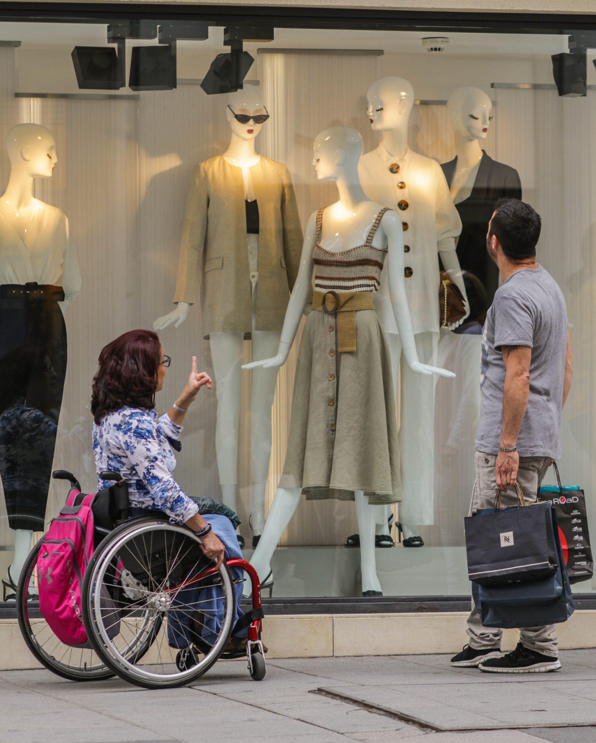 un asistente y una persona en silla de ruedas mirando un escaparate