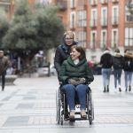 Una mujer en silla de ruedas acompañada de su asistenta personal yendo por la calle