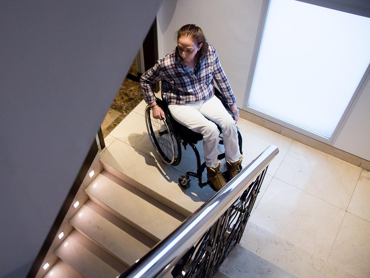 Una mujer en silla de ruedas en el descansillo de una vivienda mirando hacia las escaleras.