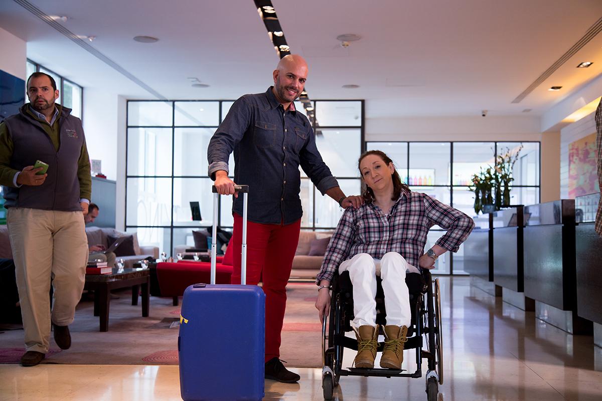 Una mujer en silla de ruedas con su asistente personal posan en la recepción de un hotel